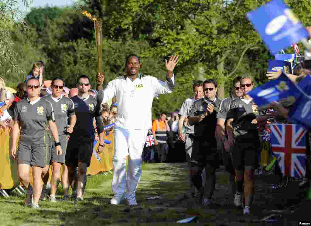 Former world heavyweight boxing champion Lennox Lewis carries the Olympic torch through Danson park in Bexley, south east London as part of the torch relay ahead of the London 2012 Olympic Games July 22, 2012.