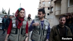 Members of OCHA (Office for the Coordination of Humanitarian Affairs), part of the United Nations, walk in the rebel held besieged town of Kafr Batna, on the outskirts of Damascus, during a distribution of humanitarian aid, Feb. 23, 2016.