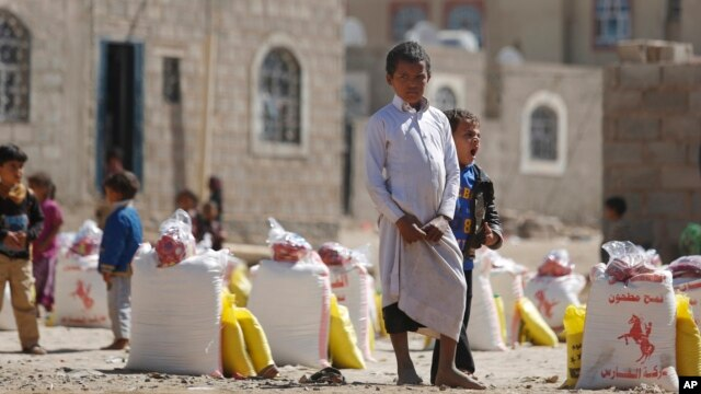 FILE - A displaced boy who fled Saada province, northwest of Sana'a with his family, waits for relief supplies during a food distribution by Yemeni volunteers in Sanaa, Yemen, Dec. 17, 2015.