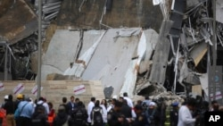 A crowd gathers around the partially collapsed Artz Pedregal shopping mall on the south side of Mexico City, July 12, 2018.