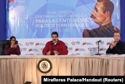 Venezuela's President Nicolas Maduro (C) speaks during a meeting with pro-government governors and mayors, next to Venezuela's National Constitutional Assembly Delcy Rodriguez (L) and Venezuela's Vice President Tareck El Aissami, at Miraflores Palace in C