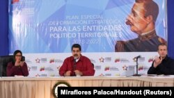 FILE - Venezuela's President Nicolas Maduro (C) speaks during a meeting with pro-government governors and mayors, next to Venezuela's National Constitutional Assembly Delcy Rodriguez (L) and Venezuela's Vice President Tareck El Aissami, at Miraflores Palace in Caracas, Dec. 19, 2017.