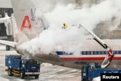 An American Airlines crew member sprays de-icing solution on a plane during a winter nor'easter snow storm in Boston, Massachusetts, Jan. 2, 2014.