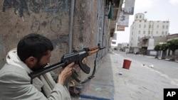 A tribesman loyal to tribal leader Sadeq al-Ahmar secures a street near al-Ahmar's house in Sana'a June 7, 2011