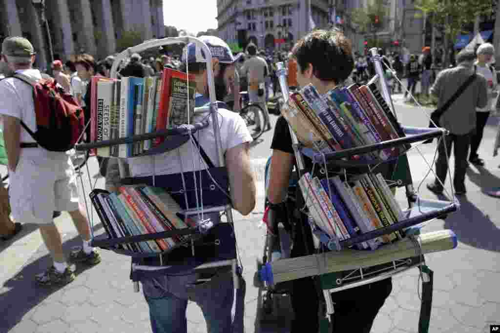 دو تن از حامیان جنبش اشغال وال استریت شماری از کتاب های مخالف خشونت را به شکل نمادین بر پشتشان حمل می کنند.