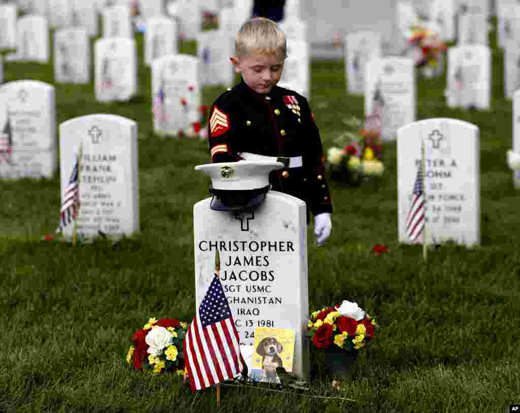 Christian Jacobs, 5, of Hertford, North Carolina, dressed as a Marine, pauses at his father's gravestone on Memorial Day at Arlington National Cemetery in Arlington, Virginia, USA.