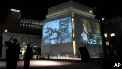 FILE - In this Monday, Nov. 20, 2006, file photo, images from Darfur and Chad are projected on the exterior walls of the United States Holocaust Memorial Museum in Washington.