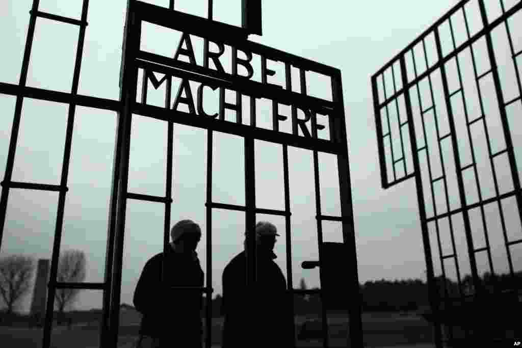 People walk through the gate of the Sachsenhausen Nazi death camp with the phrase 'Arbeit macht frei' (work sets you free) at the eve of the International Holocaust Remembrance Day, in Oranienburg, about 30 kilometers, (18 miles) north of Berlin, Jan. 26, 2015.