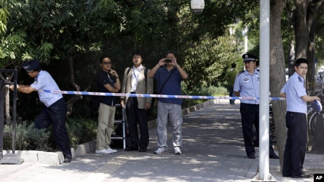 Chinese police officers set up a cordon for journalists outside the gate to the Japanese Embassy ahead of talks between Japan and North Korea in Beijing, August 29, 2012.