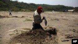 ARSIP – Seorang relawan menggali lokasi kuburan rahasia di Colinas de Santa Fe, negara bagian Veracruz, Meksiko, 30 Maret 2017 (foto: AP Photo/Felix Marquez, Arsip)