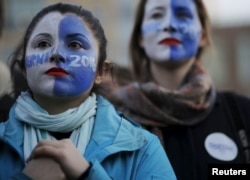 FILE - Natalia Plaza, left, and Suzanne Tufan, with their faces painted, wait for a campaign rally with U.S. Democratic presidential candidate Bernie Sanders in Washington Square Park in the Greenwich Village neighborhood of New York, April 13, 2016.
