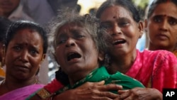 Family members of Raja Ludraswami Harjan, who died after drinking tainted liquor, cry at his funeral in Mumbai, India, June 20, 2015.