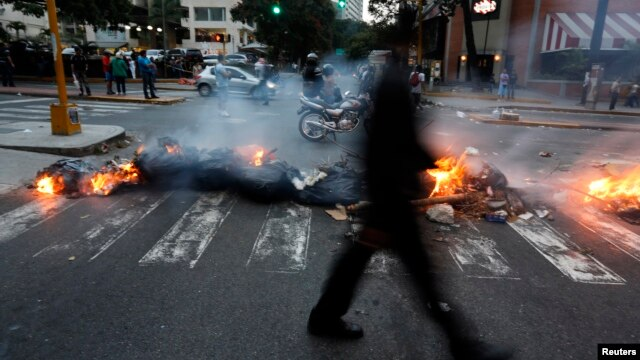 A man walks past a barricade set by anti-government protesters at Altamira square in Caracas, March 6, 2014.