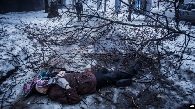 FILE - A person walks near the body of a man lying near a bus stop that was damaged in shelling in Donetsk, eastern Ukraine, Jan. 20, 2015. An estimated 9,000 people have died in the conflict in eastern Ukraine since April of 2014.