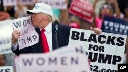 도널드 트럼프 공화당 대통령 후보에게 과거 성추행을 당했다는 여성들의 증언이 이어지고 있는 가운데, 12일 트럼프 후보가 플로리다주 레이크랜드 유세에서 '트럼프를 지지하는 여성들'이라고 적힌 선거홍보물에 입을 맞추고 있다.