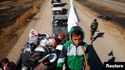 在伊拉克摩蘇爾附近的一個村莊,一名男孩在家人逃離與伊斯蘭國激進分子的戰鬥時手舉一面白色旗幟(2016年11月3日)