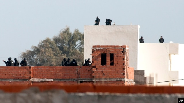 Tunisian anti-terrorist police forces (BAT) stand on roofs near a house where suspected Islamist militants were hidden in Raoued, near Tunis, Tuesday, Feb.4, 2014.