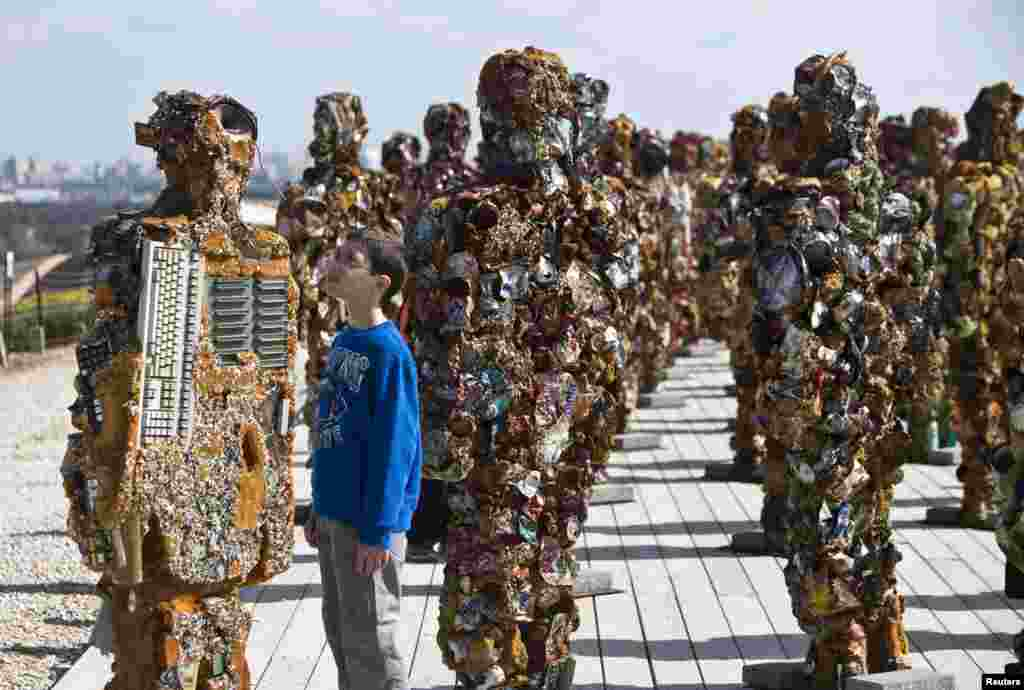 "A boy looks at a statue by German artist HA Schult during a preview of the artist's ""Trash People"" exhibition at the Ariel Sharon Park near Tel Aviv, Israel. The exhibition, featuring 500 human-sized figures made from recycled materials, has been travelling worldwide for 18 years and opens this weekend near Tel Aviv."