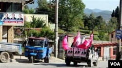 Sebuah kendaraan dengan poster kampanye pemilu lokal berkeliling kota Tirana di Albania, Sabtu (7/5).