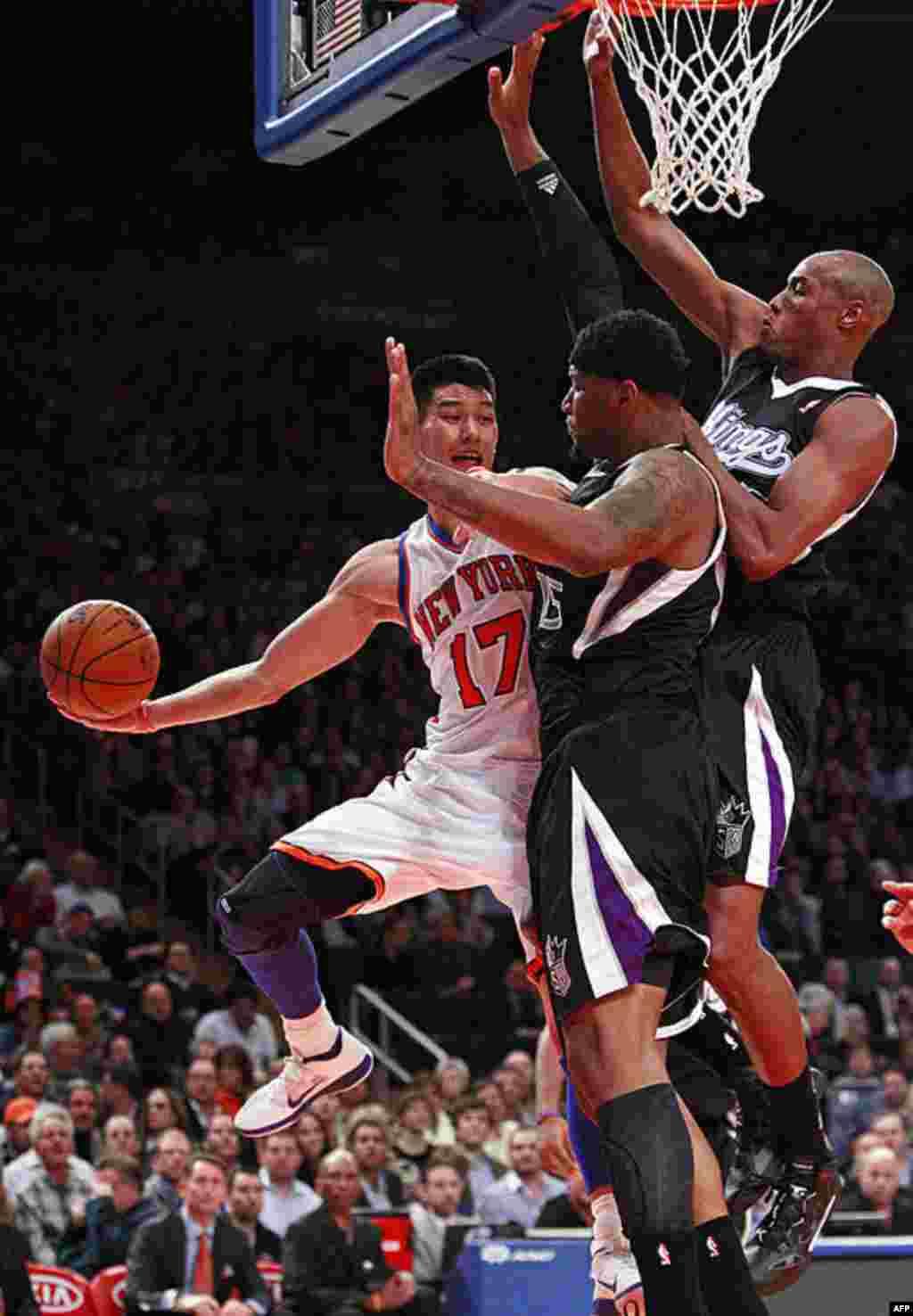Jeremy Lin vượt qua DeMarcus Cousins (giữa) của đội Kings và Travis Outlaw (phải) để ném bóng vào rổ trong hiệp đầu của trận đấu của NBA hôm 12/2/12 ở New York (AP)