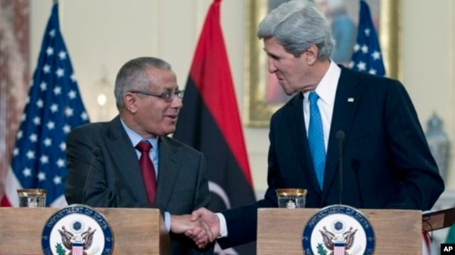Libyan Prime Minister Ali Zdidan, shown here shaking hands with U.S. Secretary of State John Kerry March 13, 2013, is under pressure to stop the crippling oil industry strikes.