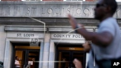 St. Louis county police officer stands inside headquarters as protesters march while grand jury begins hearing evidence to weigh possible charges against Ferguson patrolman who fatally shot 18-year-old Michael Brown, Clayton, Mo., Aug. 20, 2014.