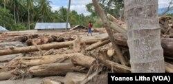 Para Relawan Kemanusiaan menyeberangi Sungai yang mulai surut untuk mengantarkan logistik bantuan bahan makanan bagi warga terdampak banjir bandang di dusun 3, Desa Bangga, Dolo Selatan, Kabupaten Sigi, Sulawesi Tengah, 1 Mei 2019. (Foto: VOA/Yoanes Litha
