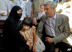 FILE - U.N. High Commissioner for Refugees Filippo Grandi talks to an Afghan refugee woman during his visit to the UNHCR's Repatriation Center in Peshawar, Pakistan, June 23, 2016.