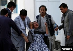 An Afghan woman mourns at the hospital after a blast in Kabul, Afghanistan, July 15, 2018.