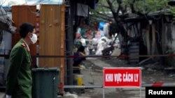 Một công an đeo khẩu trang chống khuẩn đứng gác bên ngoài khu cách ly người nhiễm virus corona ở Hà Nội hôm 13/3. Chính phủ Việt Nam quyết tâm giữ cho số ca nhiễm Covid-19 dưới mức 1.000.