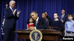 U.S. President Barack Obama signs executive orders on gun violence during an event at the White House in Washington, January 16, 2013.