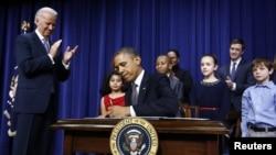 Presiden Obama menandatangani 23 perintah eksekutif untuk memerangi kekerasan senjata api, di Gedung Putih, Washington D.C., disaksikan oleh Wapres Joe Biden dan sebagian dari murid dan keluarga korban penembakan di SD Sandy Hook, Connecticut (16/1).