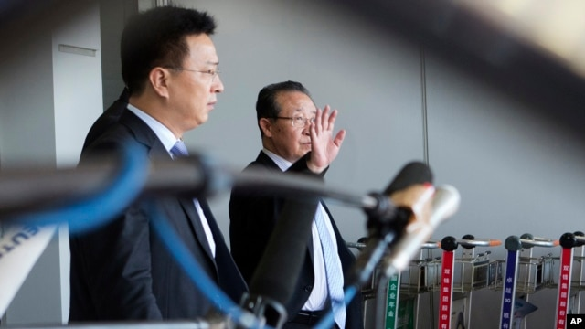 North Korea's First Vice Foreign Minister Kim Kye Gwan, right, waves as he arrives in Beijing, China, June 18, 2013.