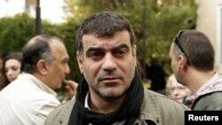 """Redaktur majalah mingguan """"Hot Doc"""", Costas Vaxevanis menunggu di luar gedung pengadilan di Athena, Yunani (Foto: dok). Vaxevanis kembali diadili setelah mempublikasikan nama ribuan warga Yunani pemilik rekening bank di Swiss (16/11)."""