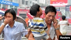 Un homme transporte un enfant secouru après un incendie dans l'immeuble d'une école maternelle à Ningde, dans la province de Fujian, Chine, 16 septembre 2015.