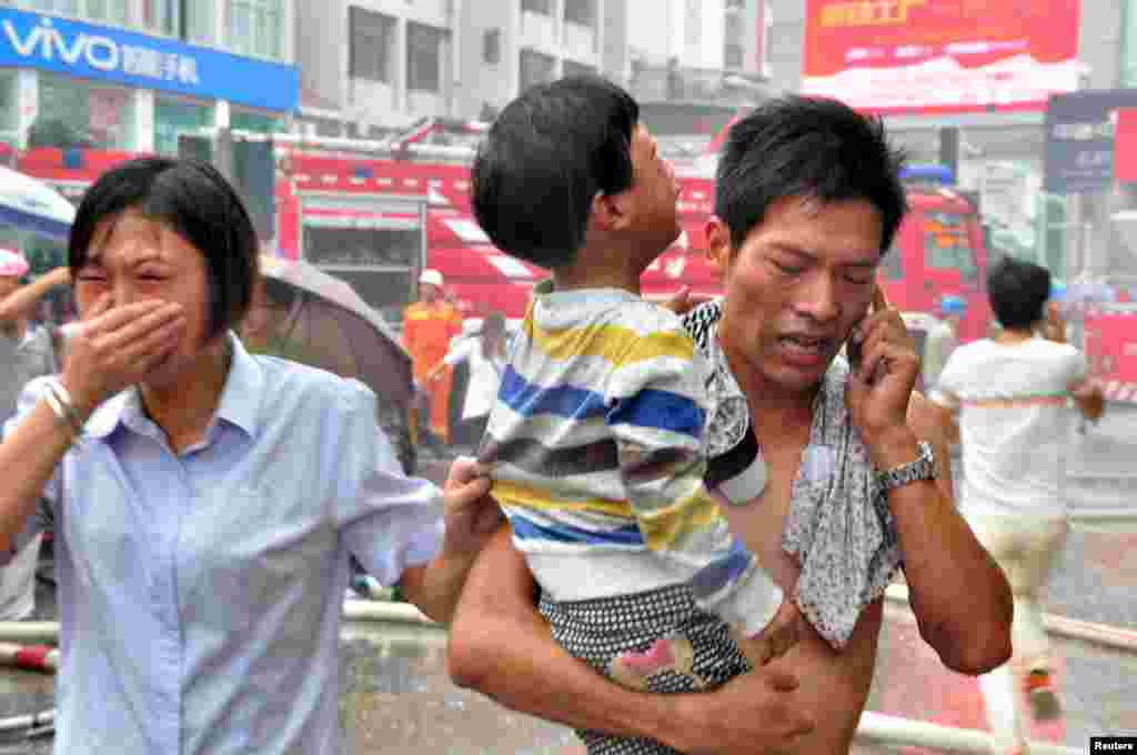 A man holds a child after rescuing him from a kindergarten affected by a fire at a commercial building, in Ningde, Fujian province, China. According to local media, more than 260 people were evacuated due to the fire. No causalities have been reported and the cause of it is still unknown.
