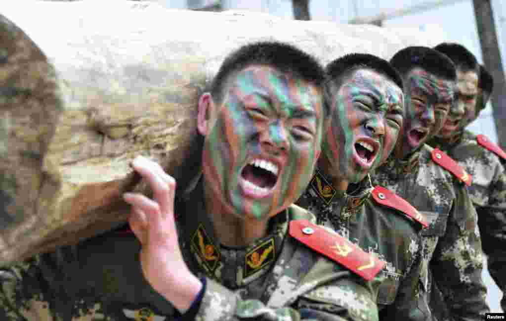 Paramilitary policemen shout as they lift a log during a winter training session at a military base in Chaohu, Anhui province, China.