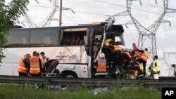 Des pompiers évacuent des adolescents d'un bus endommagé après un accident sur l'autoroute entre Lille et Paris près de Gravelines, dans le nord de la France, 1er juin 2017.