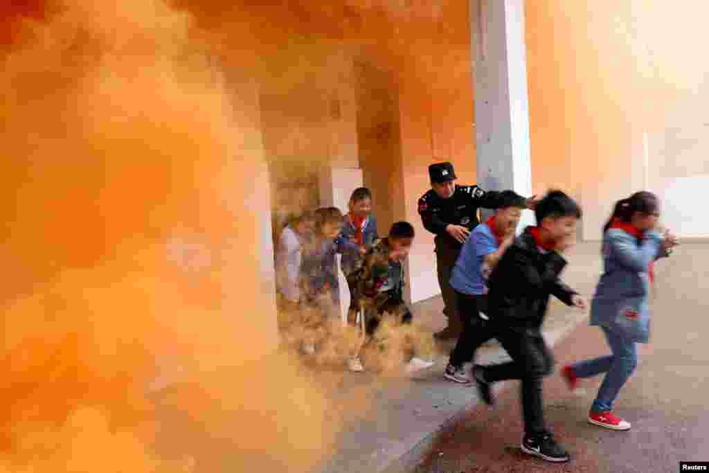 A police officer and schoolchildren take part in an anti-terrorism drill at a primary school in Huaibei, Anhui province, China, May 7, 2018.