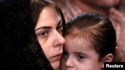 Женщина с дочерью на поминальной церемонии по погибшим в августовской войне (архивное фото)