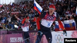 Russia's Alexander Legkov and Ilia Chernousov (L) race to the finish line to take first and third place in the men's cross-country 50 km mass start free event at the Sochi 2014 Winter Olympic Games, Feb. 23, 2014.