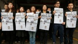 Editorial staff members of the Ming Pao newspaper hold the front page of their newspaper with the headline on the former editor Kevin Lau, who was assaulted and injured during a protest outside the Ming Pao office in Hong Kong on Feb. 27, 2014.