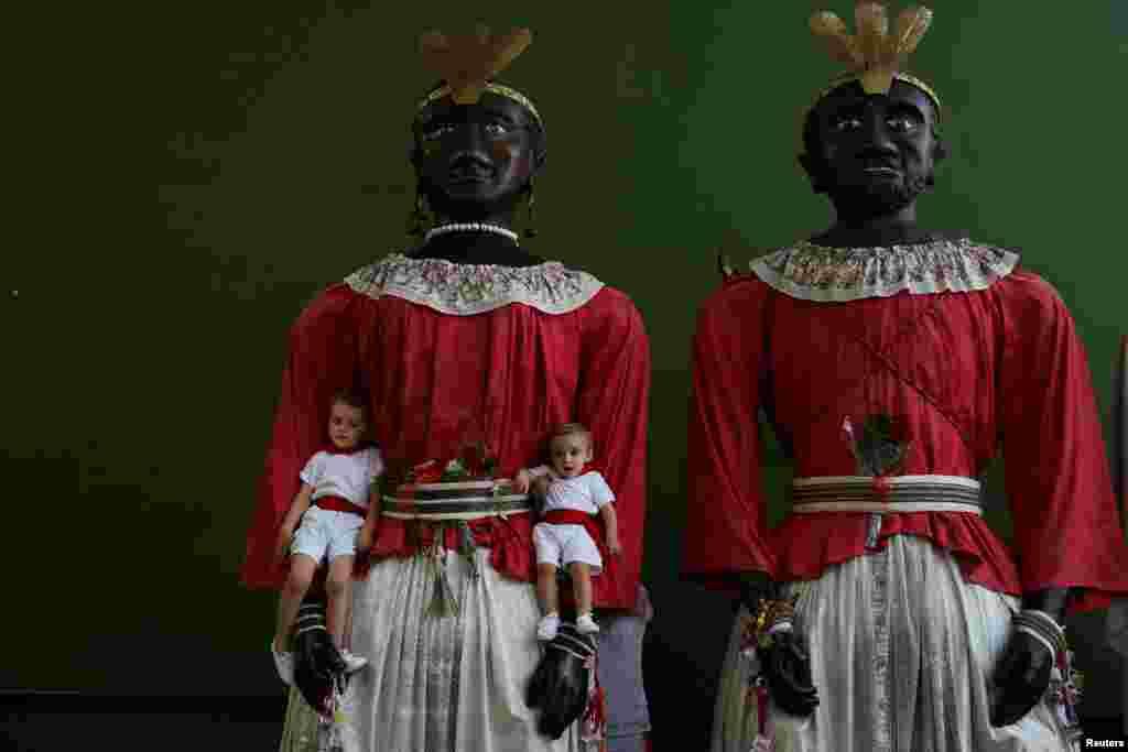 ក្មេងៗថតរូបជាមួយនឹងយក្សពីរនាក់ក្នុងការដើរក្បួន Parade of the Giants and Big Heads នៅក្នុងក្រុង Pamplona ប្រទេសអេស្ប៉ាញ។