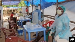 Medical personnel inside a clinic take care of Ebola patients in the Kenema District on the outskirts of Kenema, Sierra Leone, July 27, 2014.
