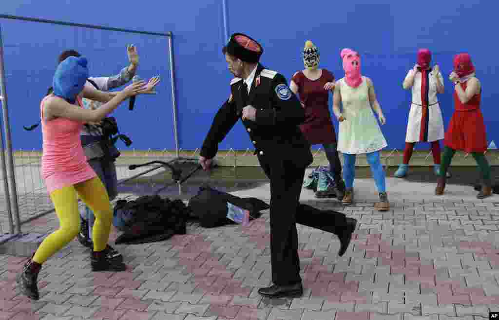 A Cossack militiaman attacks Nadezhda Tolokonnikova and a photographer as she and fellow members of the punk group Pussy Riot demonstrate in Sochi, Russia.