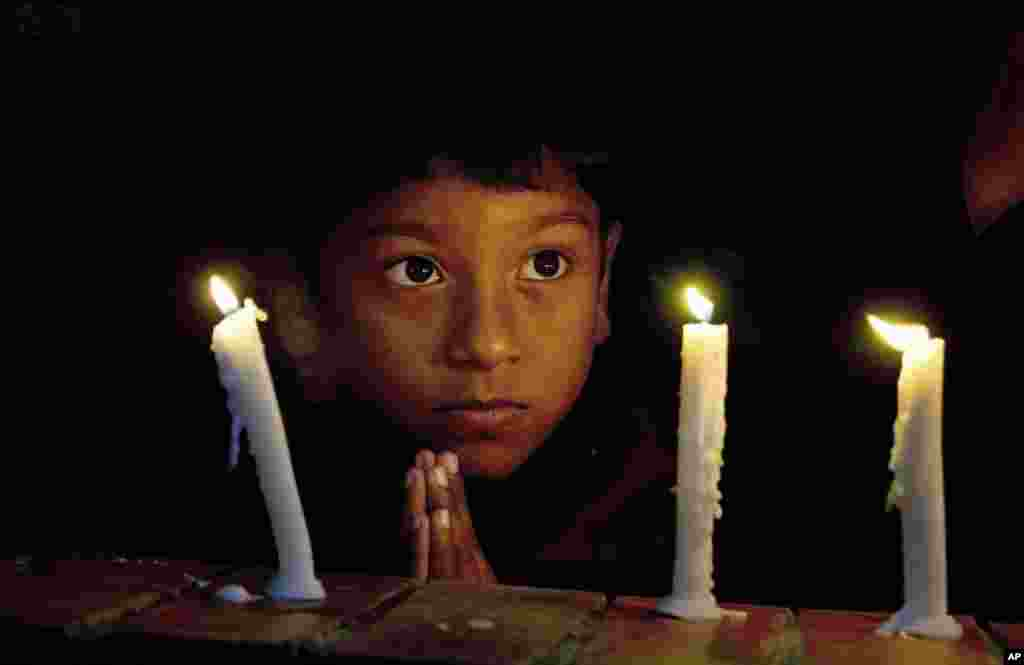A boy prays during a candlelight vigil for victims of Paris attacks, at St. Thomas Church in Islamabad, Pakistan.