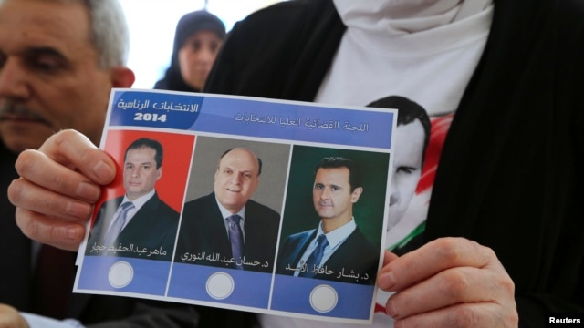 A Syrian national living in Beirut holds a ballot paper with pictures of the three presidential candidates, (from L-R) Maher Abdul-Hafiz Hajjar, Hassan Abdallah al-Nouri and Syria's President Bashar al-Assad, as she casts her vote ahead of the June 3 presidential election at the Syrian Embassy in Yarze, east of Beirut, Lebanon, May 28, 2014.