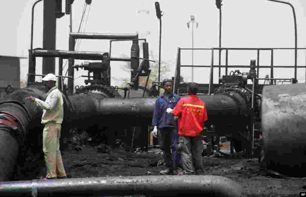 """""""Is it true that the government of Sudan has decided to allow South Sudan to export oil through its territory? I will only believe when I see oil flowing."""" Wen Nyan in Juba Sudanese workers inspect burnt out oil pipes at the border town of Heglig, Sudan, April 24, 2012 (file photo)."""