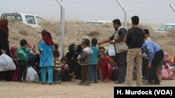Families wait by the fence as soldiers screen incoming refugees in Khazir Camp in the Kurdish region of northern Iraq, Oct. 28, 2016.