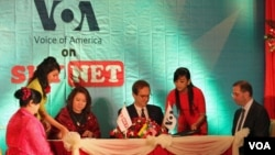 VOA Director David Ensor (center right) along with Myint Myint Win (center left), Managing Director of Sky Net, sign the agreement to broadcast VOA content to Burma. US Ambassador Derek Mitchell (right) looks on.